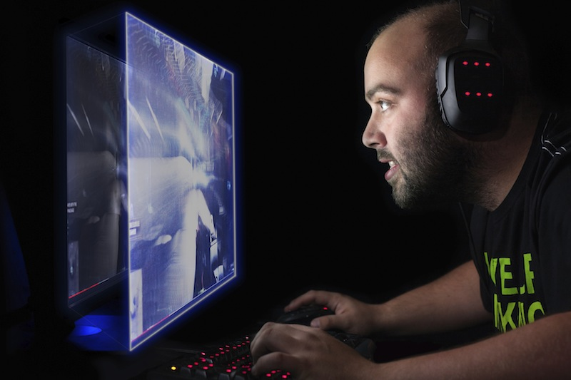 Male gamer wearing headphones while looking at a computer screen.
